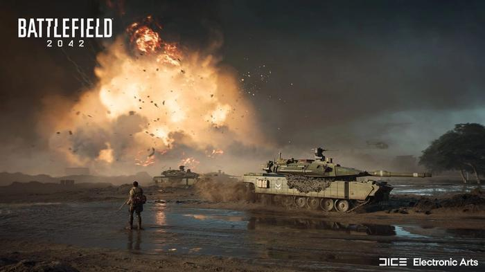 An explosion fires in the distance as a soldier stands next to a tank in a muddy bog