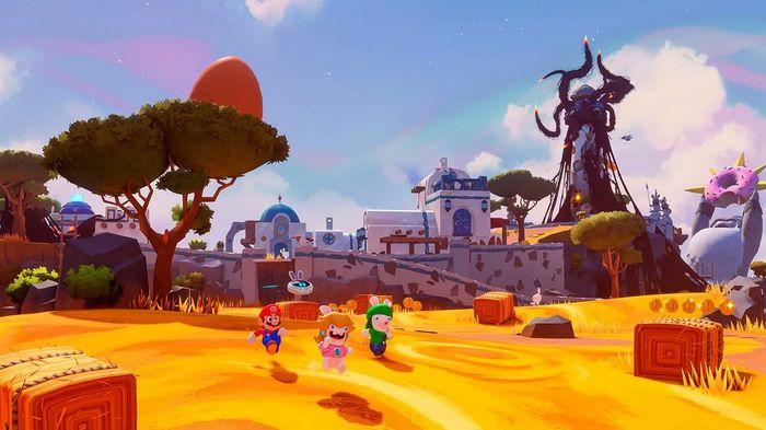 The image shows Mario, Rabbid Luigi, and Rabbid Peach walking along a field.