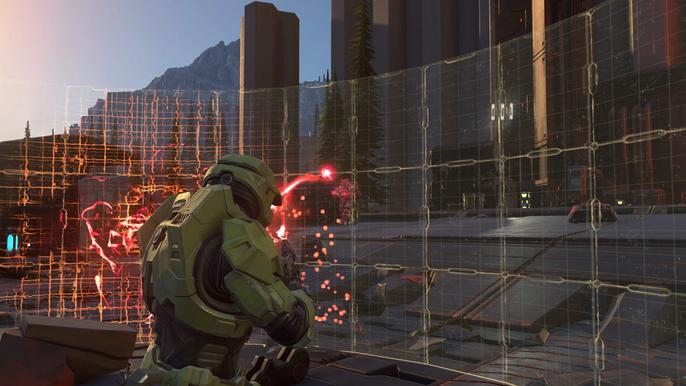 Halo Infinite's Master Chief shoots enemies from behind a shield.