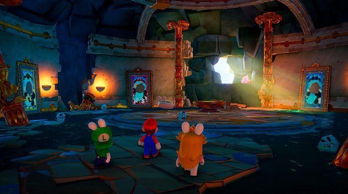 This image shows Rabbid Luigi, Rabbid Peach and Mario standing in a large hall.