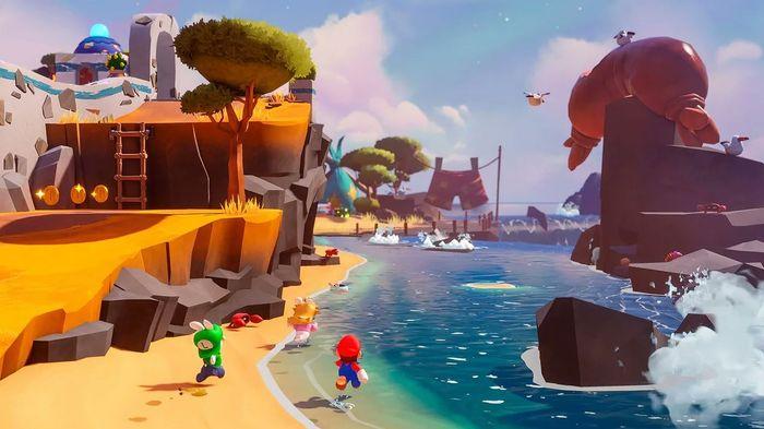 The image shows Mario, Rabbid Peach and Rabid Luigi running along a beach.