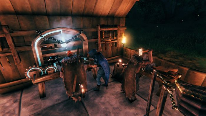 Players using the workshop in a house in Valheim. Three players use workbenches, in the corner of a large wooden house.