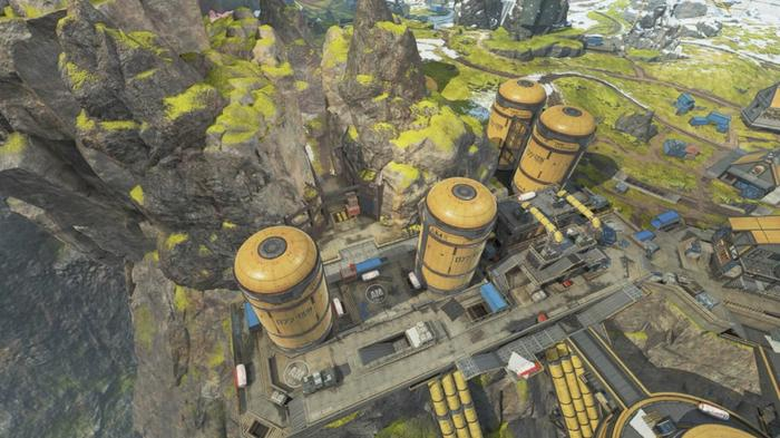 An overhead shot of huge silos, with a narrow cavern running through a mountain behind them.