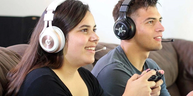 LucidSound LS35X Wireless Gaming Headset - Promotional image showing two adults playing games, woman is wearing the Rose Gold/White LS35X headset. Man is wearing a Black LS35X headset.