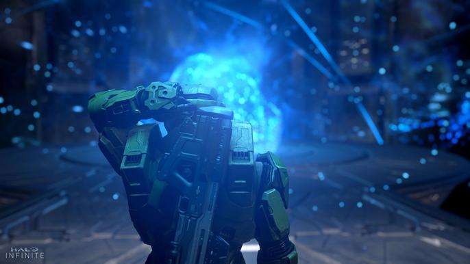 Master Chief stands in front of a giant blue orb of light.