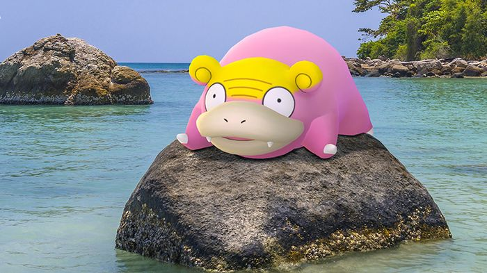 A Galarian Slowpoke, completely pink except for a yellow scalp, sits on a rock in the ocean, looking confused.