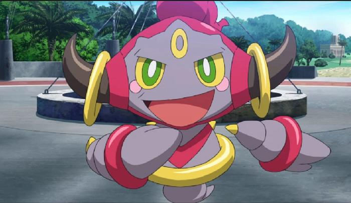 Hoopa floats above a pavement with a mischievous smile.
