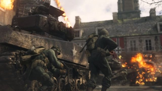 World War 2 Soldiers standing near tank while another tank in front explodes
