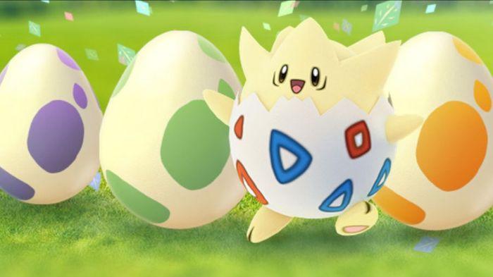 A Togepi stands next to three Pokémon GO eggs.