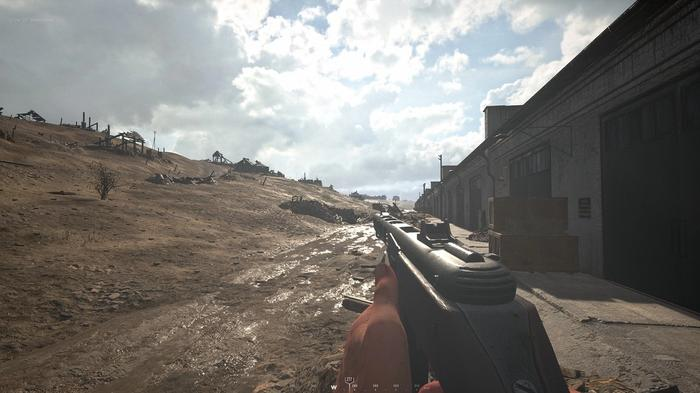 Hell Let Loose screenshot showing a player aiming their weapon with buildings on one side and a hill on the other.